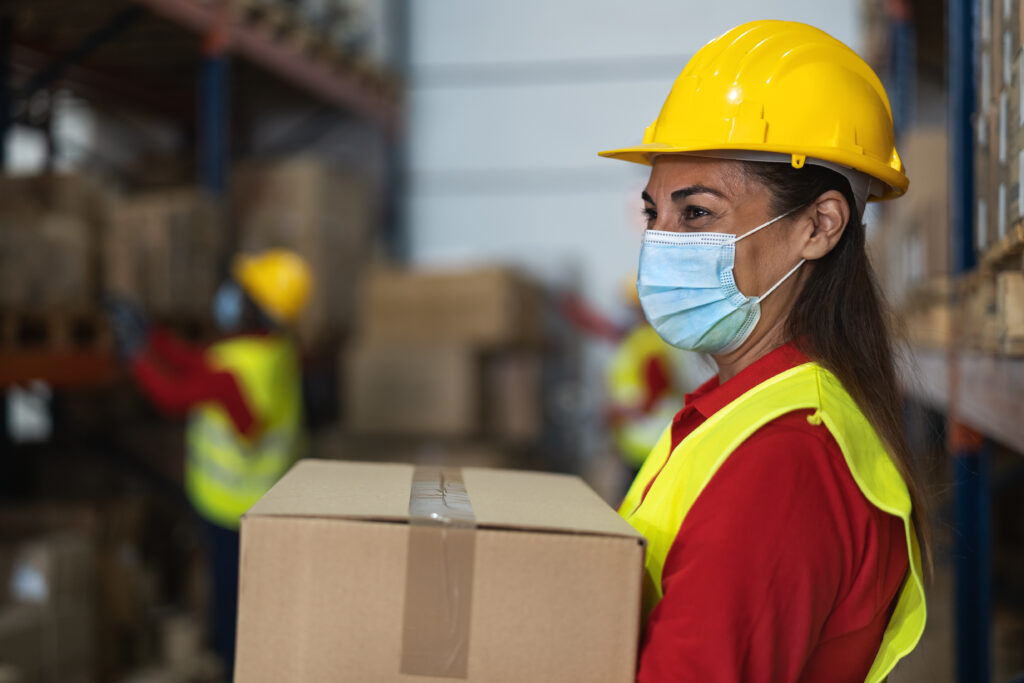 Arbeiterin mit Helm und Corona-Maske