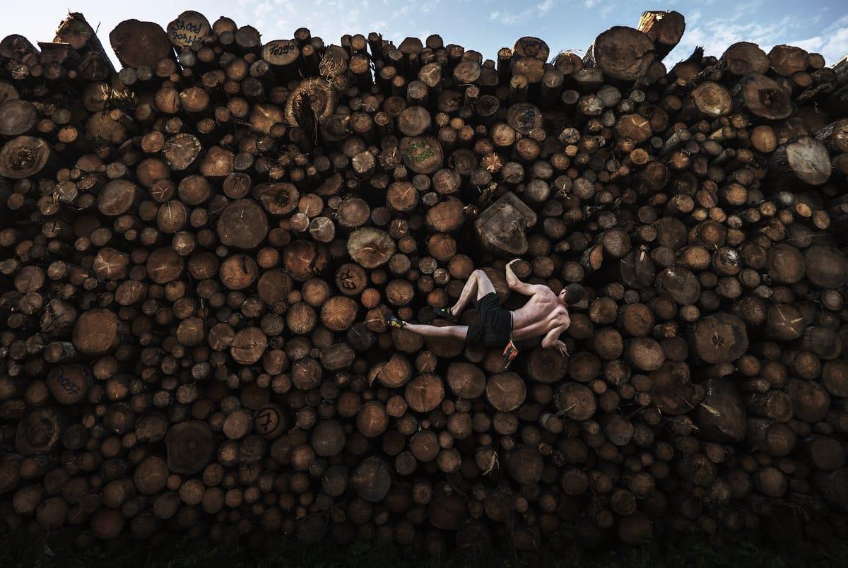 Ein Mann klettert einen Holzstapel entlang