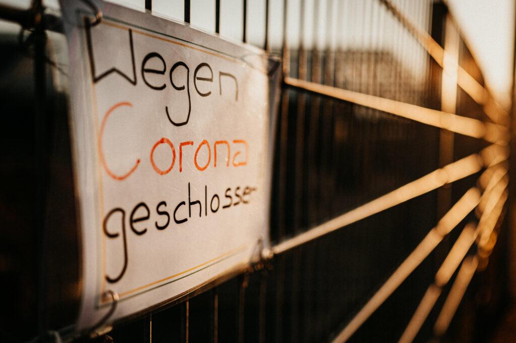 Schild wegen Corona geschlossen am Zaun eines Betriebsgeländes