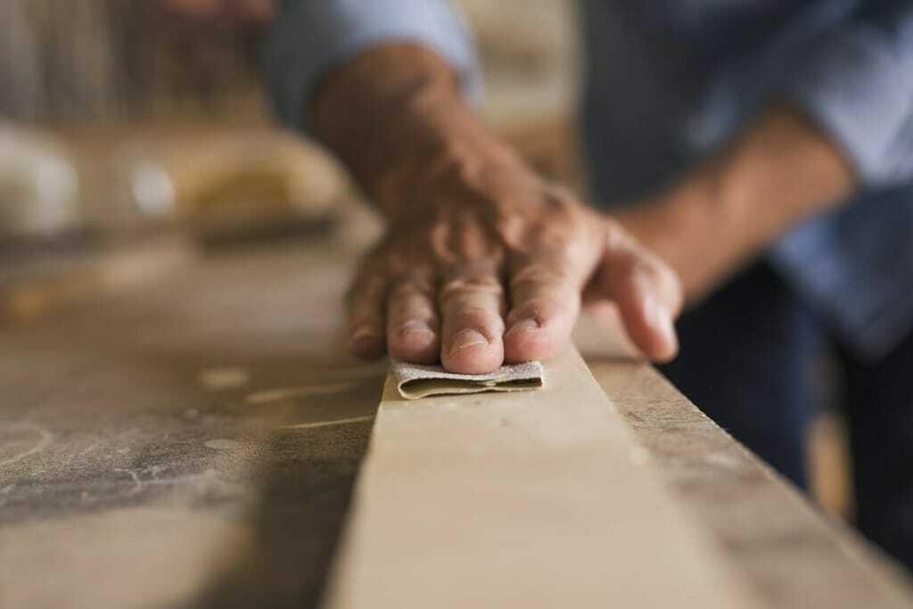 Männerhand schleift Holz.