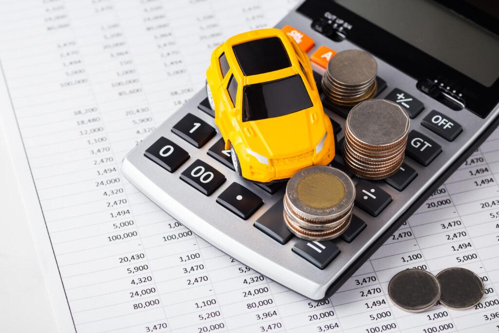 Spielzeugauto und Münzen auf Taschenrechner und Bilanz
