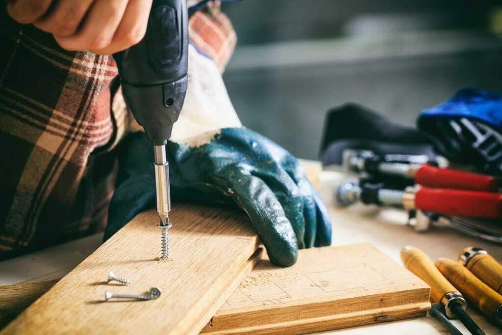 Handwerker bohrt mit Maschine in Holz.