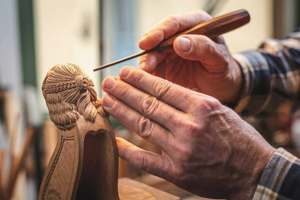 alter Mann beim Holzschnitzen