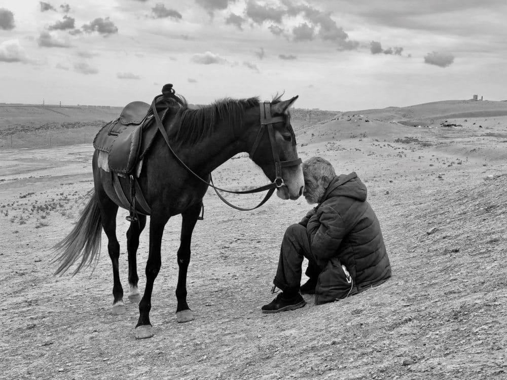 Mann sitzt vor gesatteltem Pferd in öder Landschaft
