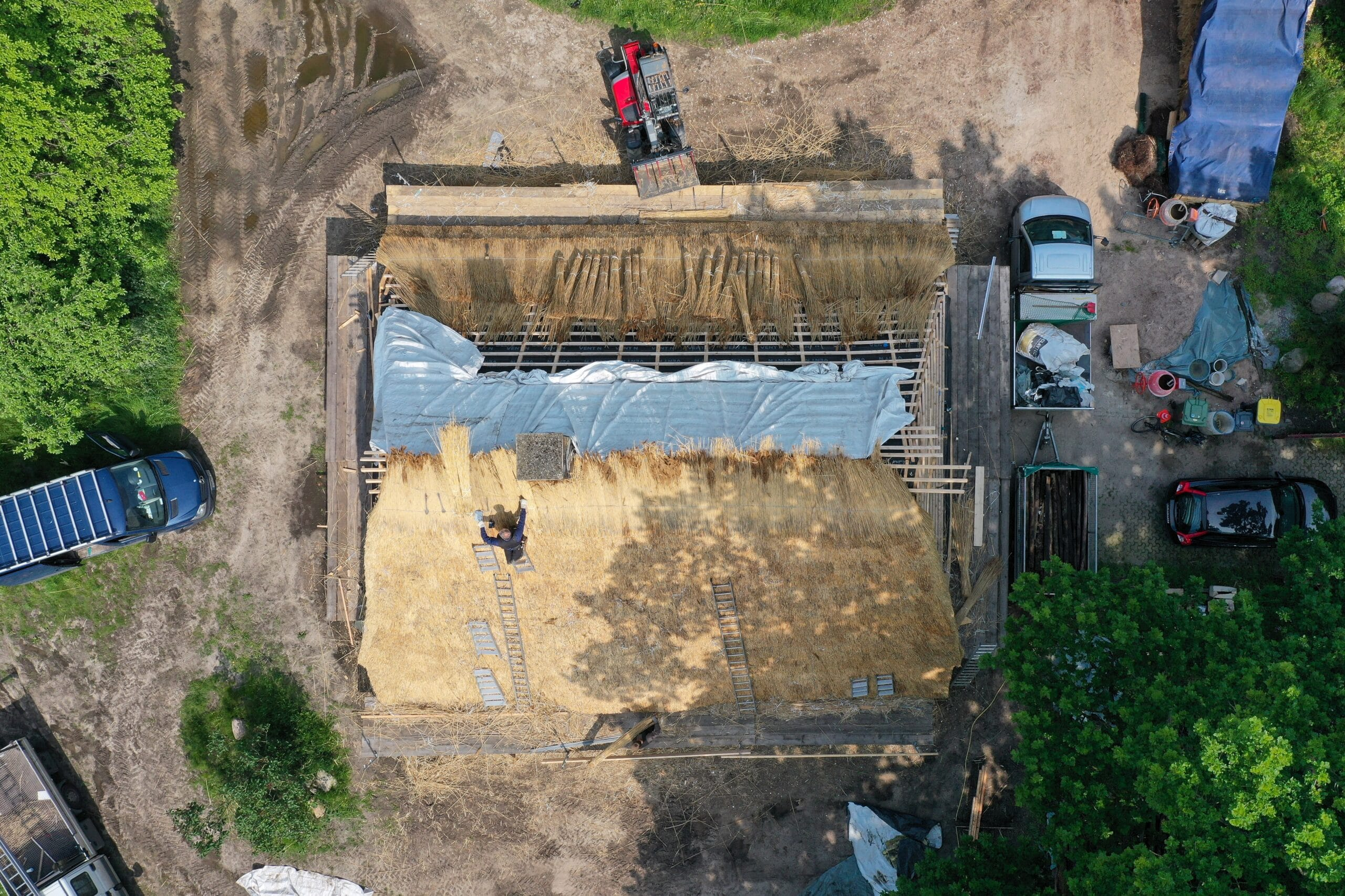 An einem Reetdach wird gearbeitet (Luftaufnahme mit einer Drohne).