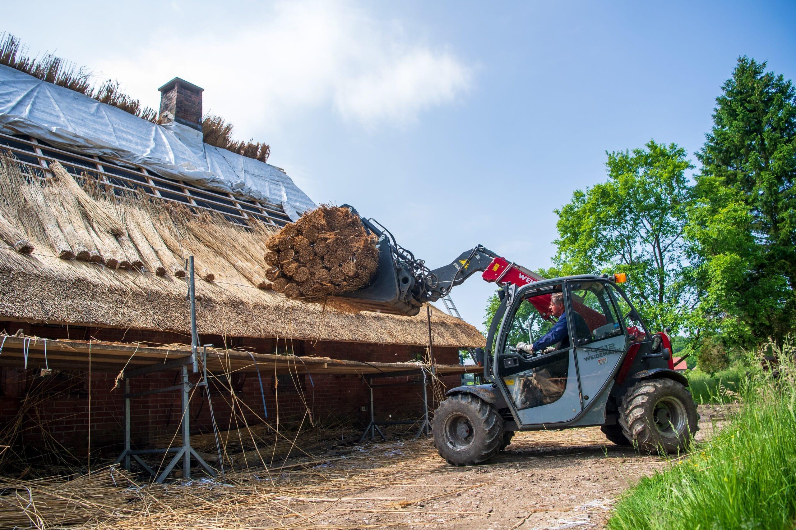 Bagger hebt Strohrollen auf ein zu deckendes Dach