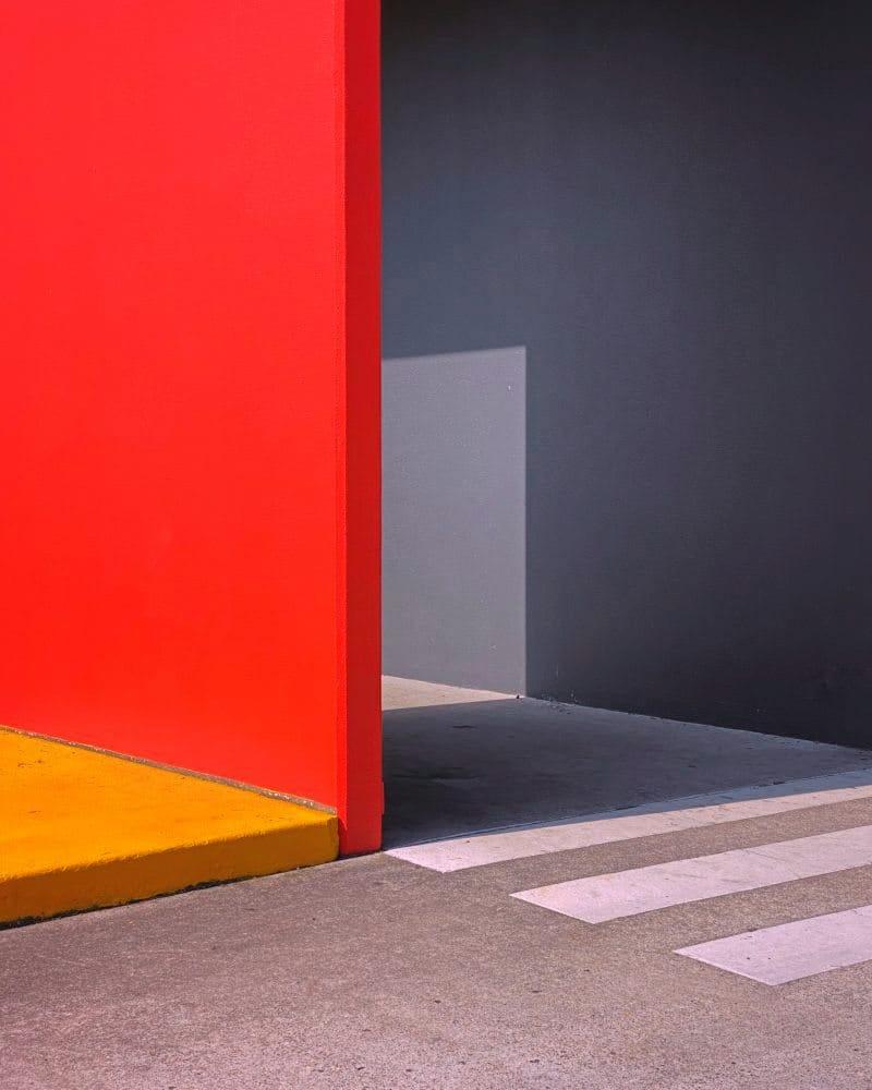 Farbige Platten stehen rechtwinklig zueinander und werfen einen Schatten an die Wand