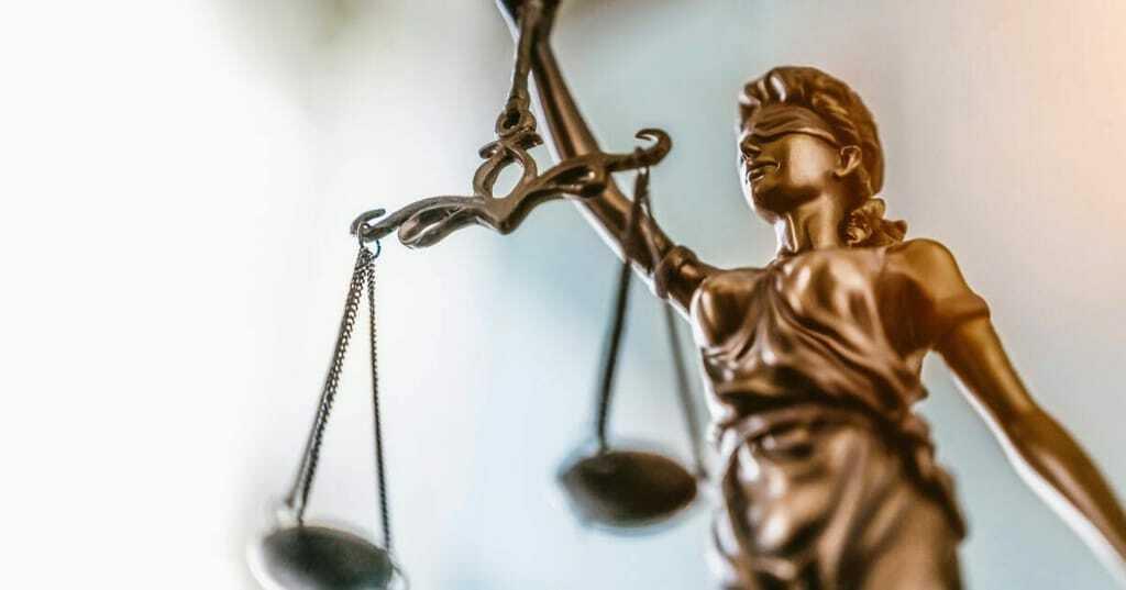 Justitia vor verschwommenem Hintergrand