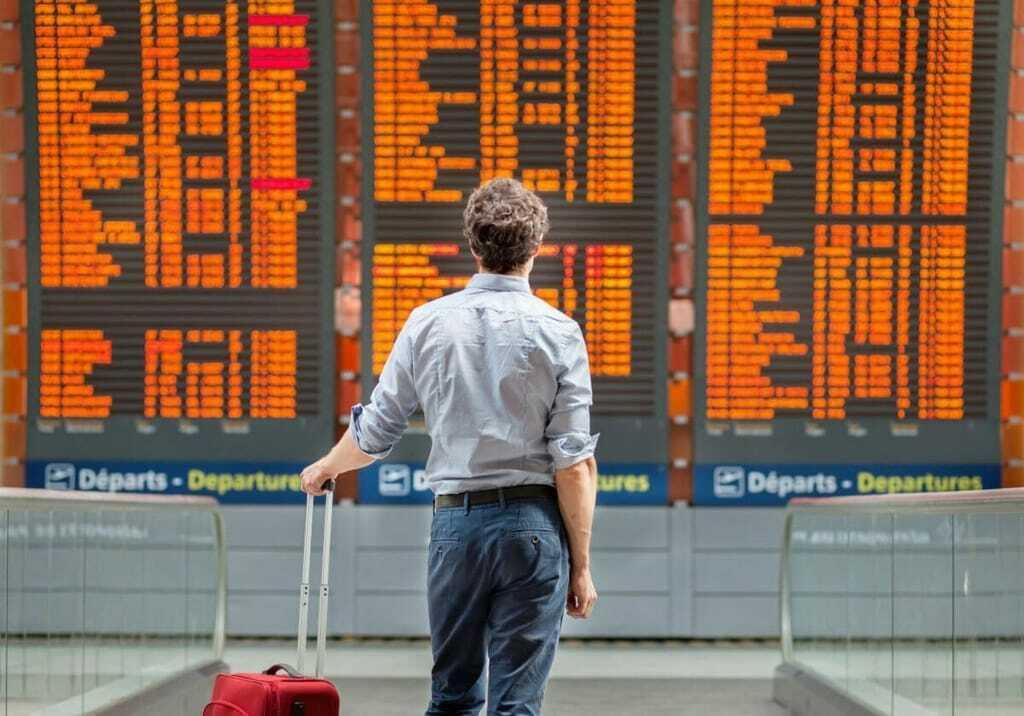 Mann steht vor Anzeigetafel im Flughafen