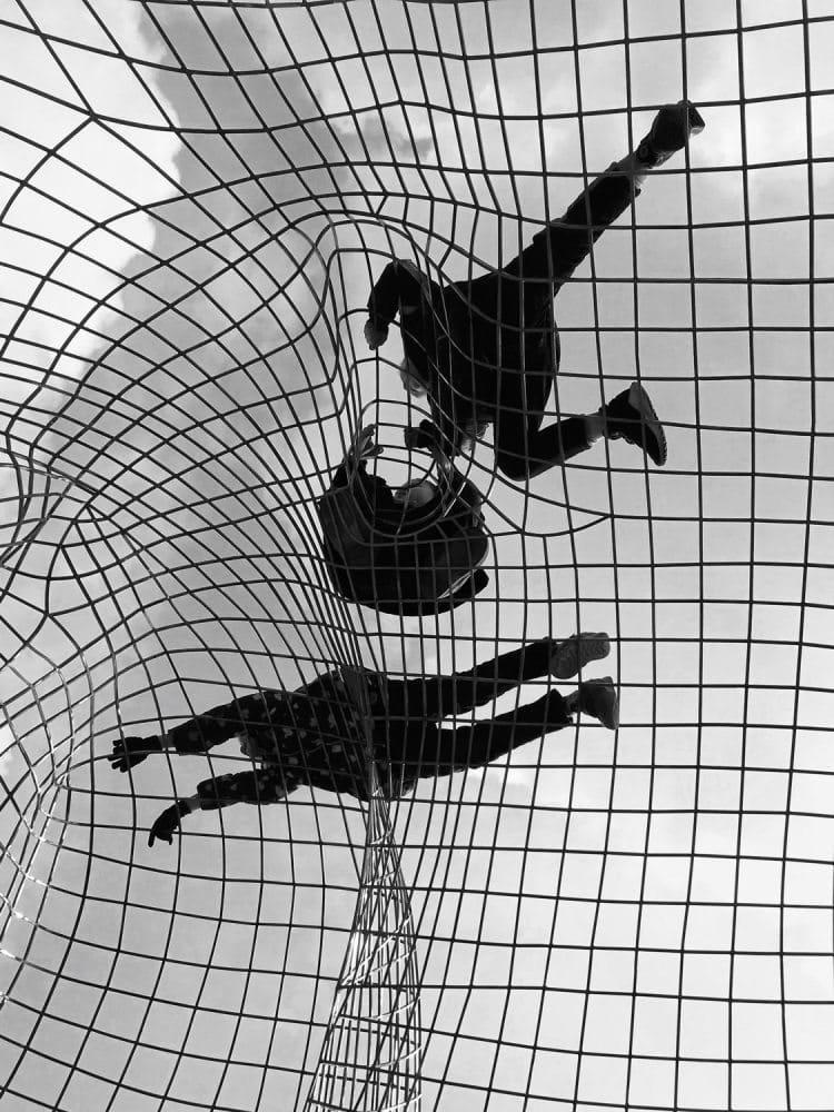 Kinder werden von unten beim Spielen auf, in Karomuster angeordneten, Metallstreben fotografiert.