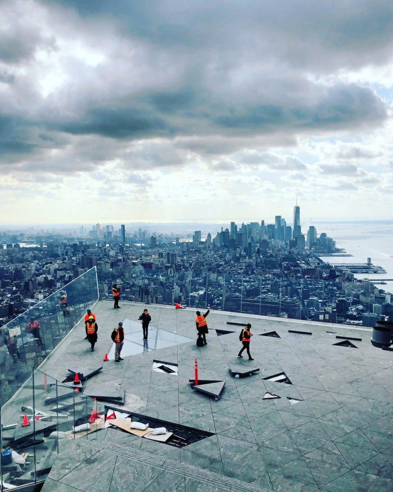 Menschen in Warnwesten bewegen sich auf einer im Bau befindlichen Aussichtsplattform