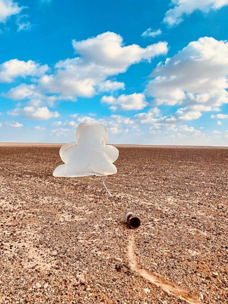 Leere, rostige Konservendose auf einem Feld, an der ein sich wolkenförmig aufblähender Fallschirm befestigt ist, vor einem blauen Himmel mit Wolken