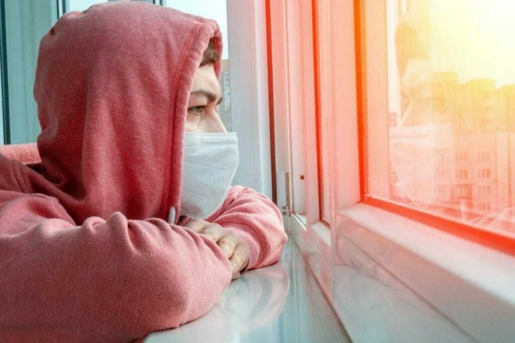 Junger Mann sitzt mit Maske vor dem Fenster