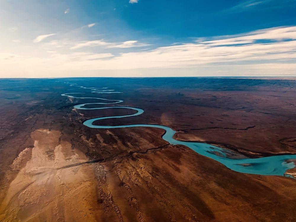 Ein mäanderförmiger Fluss durschneidet eine karge Landschaft