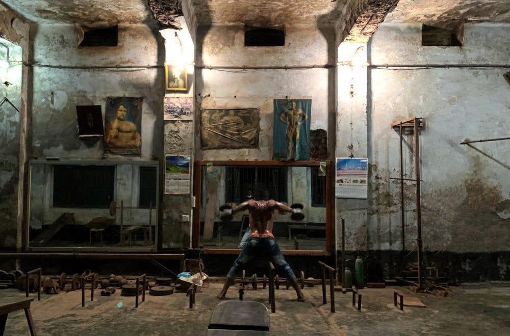 Mann trainiert mit freiem Oberkörper an einem Ort, der an eine alte Lagerhalle erinnert