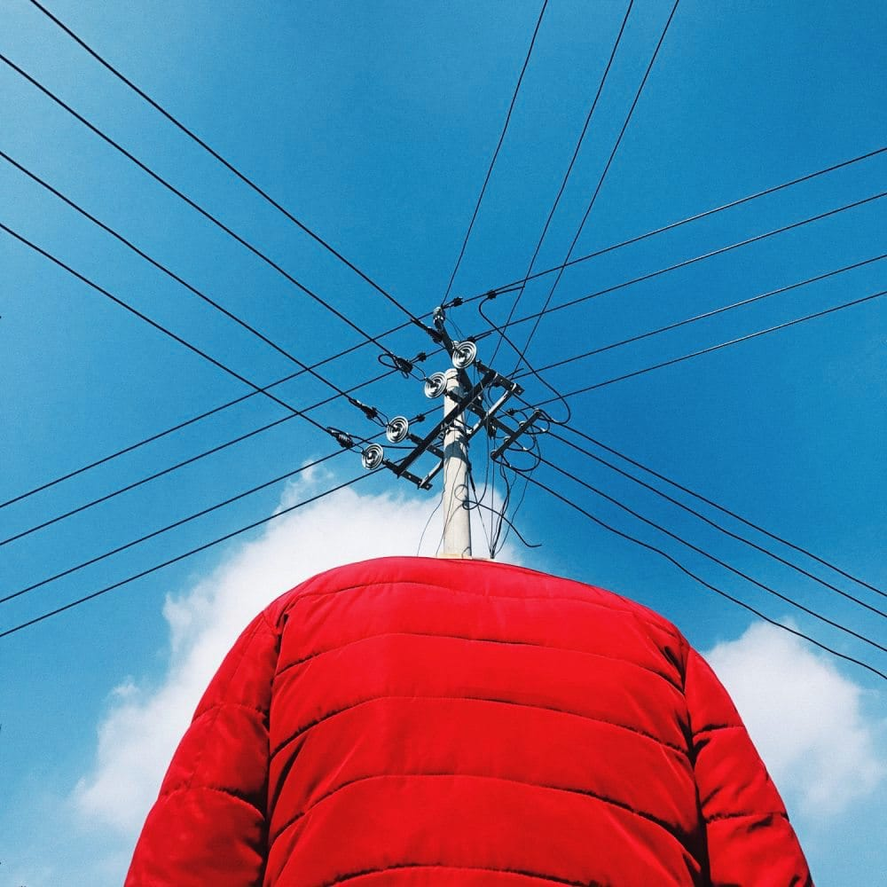 Rote Jacke vor sich kreuzenden Oberleitungen, deren Schnittstelle an der Stelle ist, wo ein Mensch seinen Kopf hätte