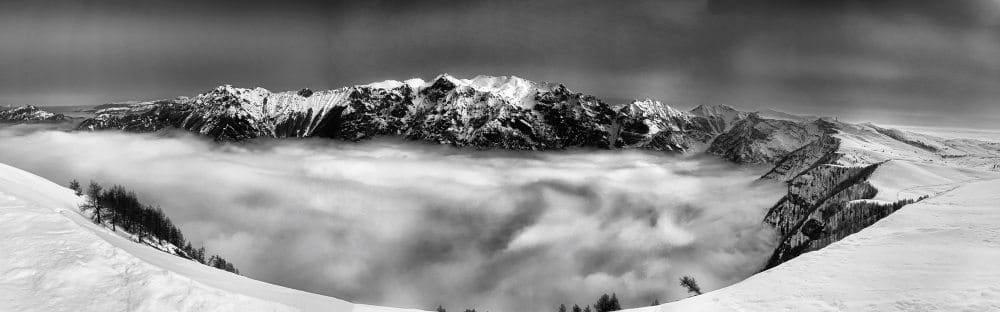 Panorama-Aufnahme von einem Hochplateau von einer gegenüberliegenden Gipfelkette und einem von tiefstehenden Wolken verhangenen Tal