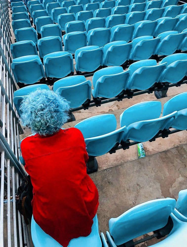 Fan mit blauem Haar und rotem T-shirt sitzt auf blauen Sitzschalen in einem Stadion