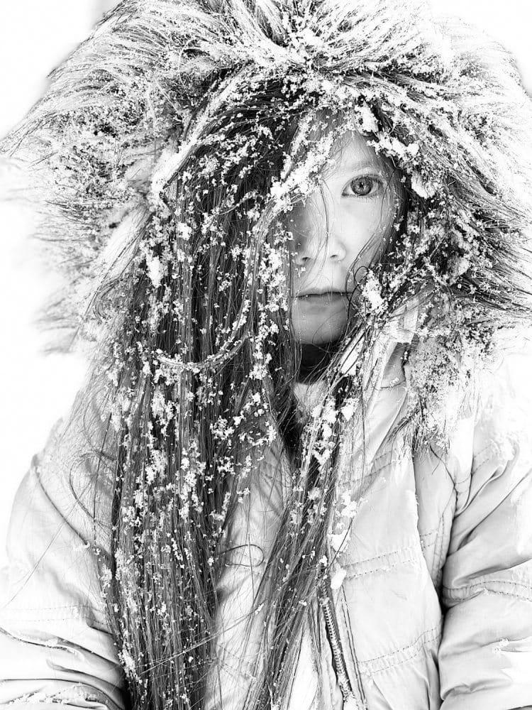 In schwarz-weiß fotografiertes, eingeschneites Mädchen in Felljacke mit hochgezogener Kapuze