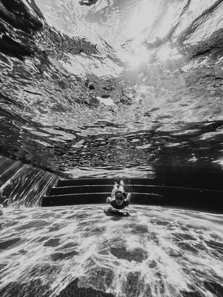 Unterwasseraufnahmen eines Mädchens beim Tauchen in einem Swimmingpool