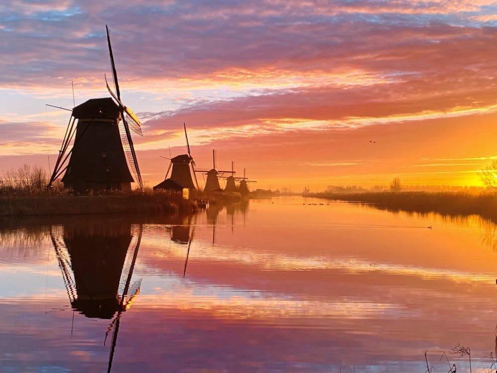 Windmühlen an einer Gracht mit untergehender Sonne