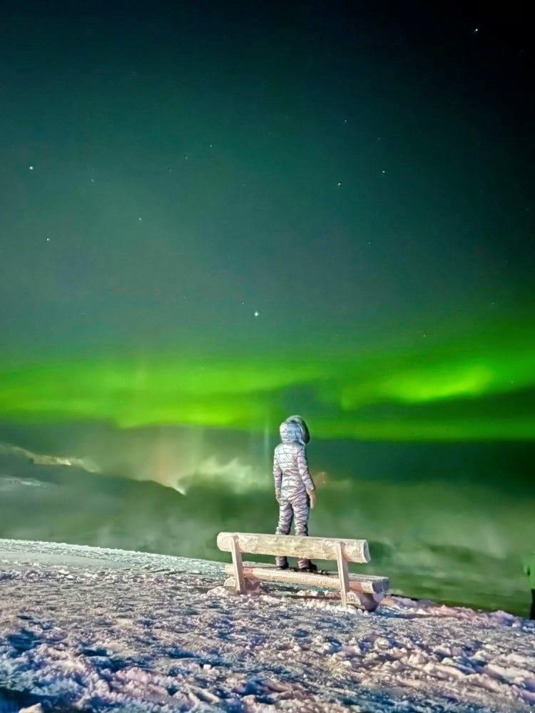 Person steht im Schneeanzug auf einer Bank im Schnee in Richtung der Polarlichter gewandt.