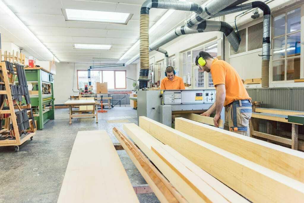Tischler verarbeiten Holz in Schreinerei.