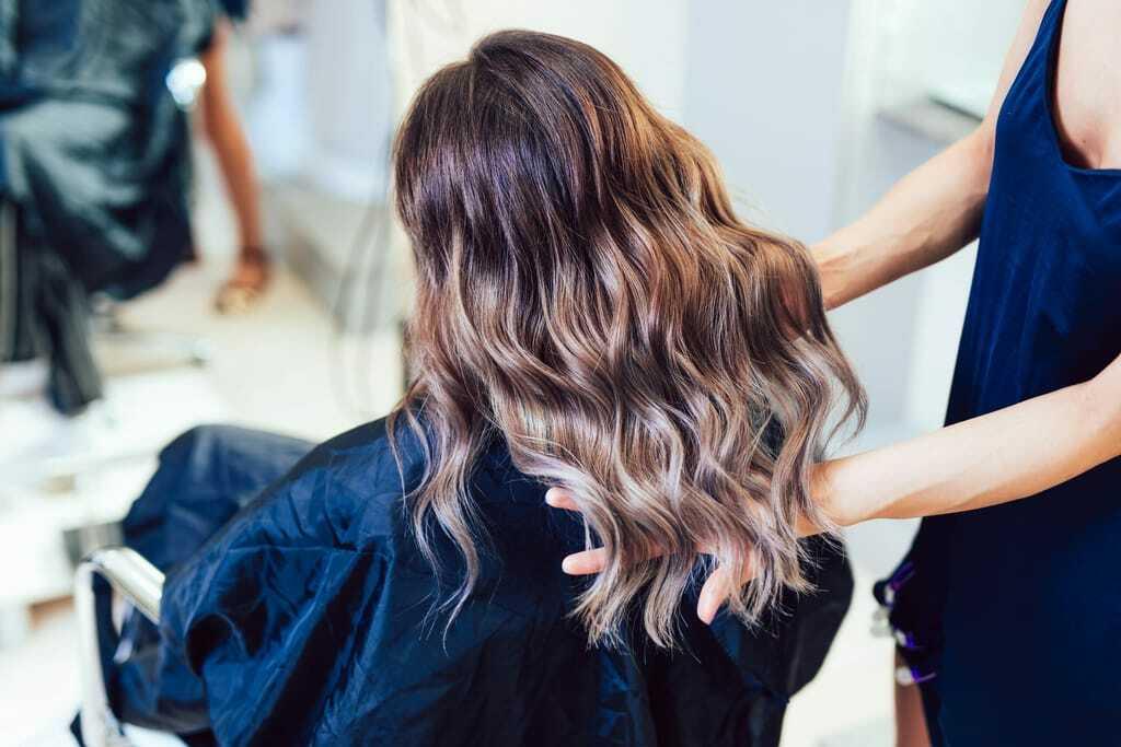 Kundin mit frisch gemachten Haaren im Salon
