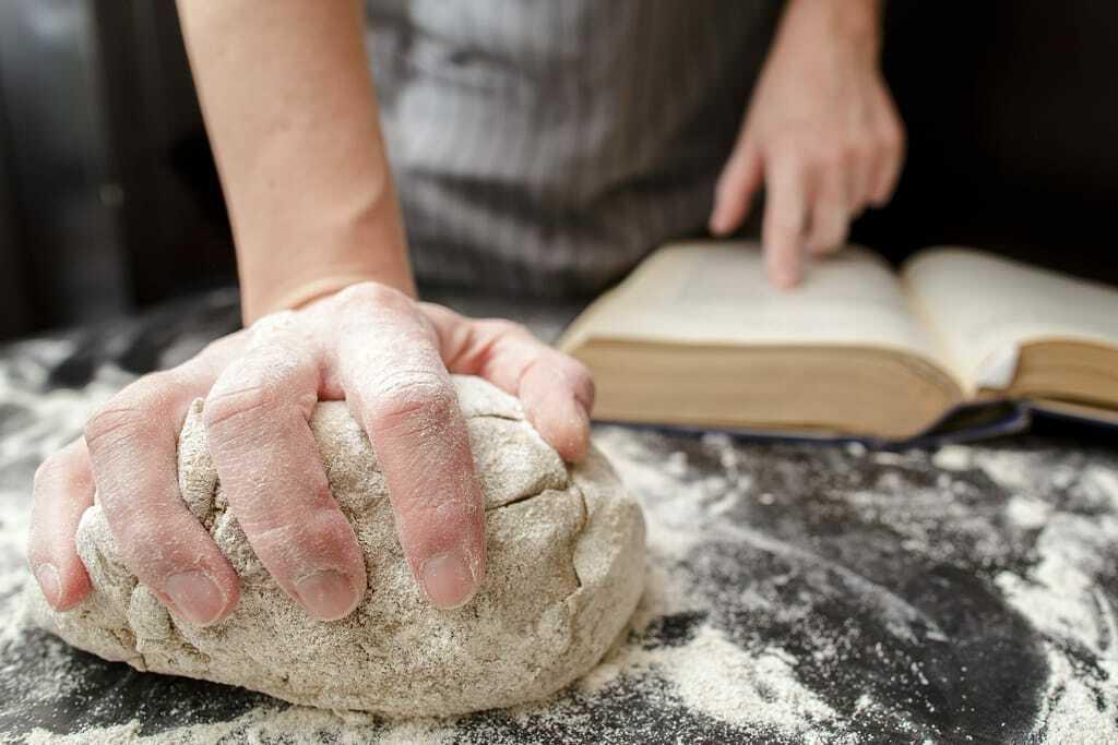 Bäcker knetet Brot und liest Handbuch.