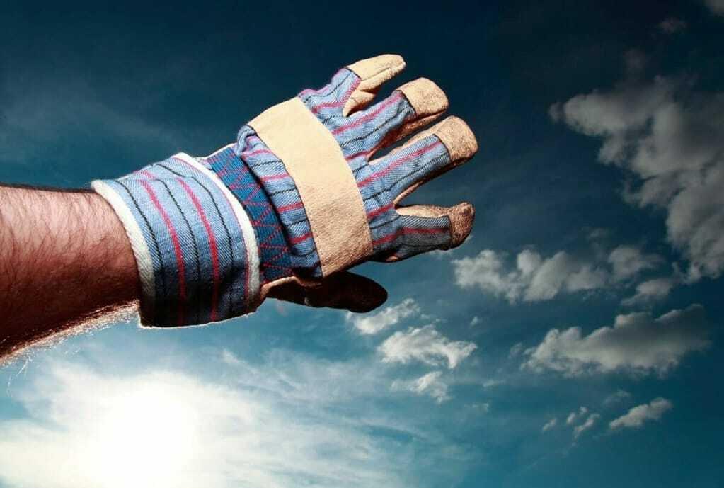 Hand in Arbeitshandschuh verdeckt die Sonne