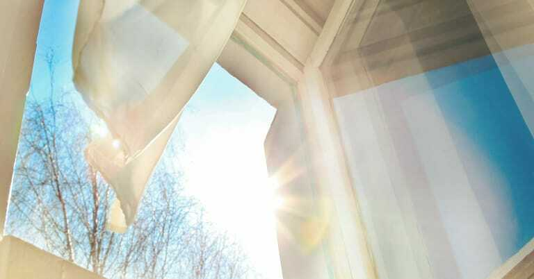 Weit geöffnetes Fenster mit Vorhang im Wind