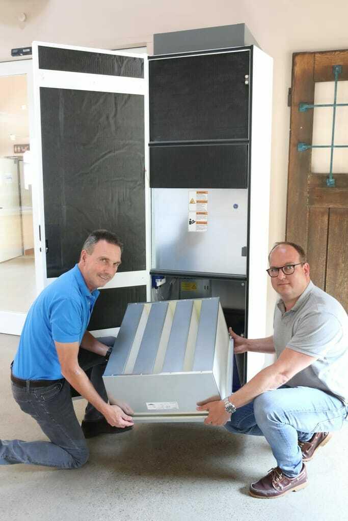 Björn Leutke und sein Onkel Matthias Leutke setzen einen Filter in einen Luftreiniger ein.