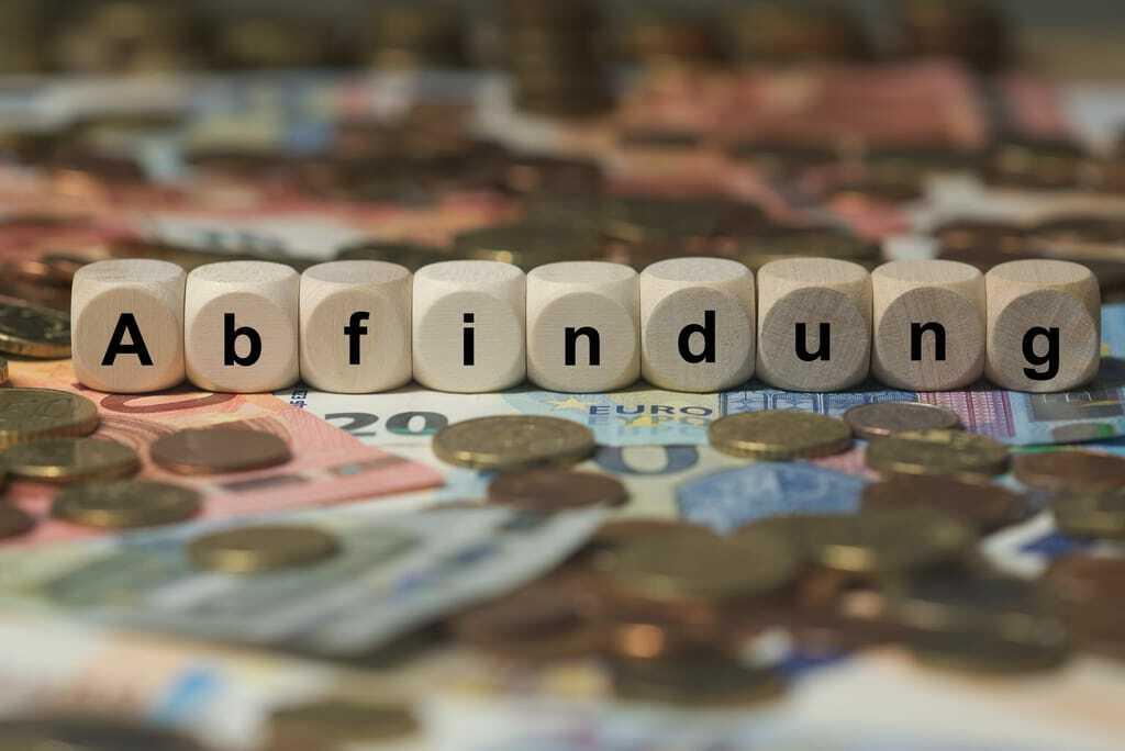 Bausteine mit Aufschrift Abfindung auf Geldscheinen.