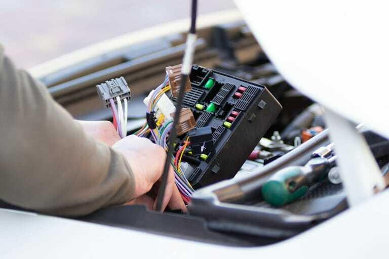 Mechaniker überprüft Autosicherung von Elektroauto.