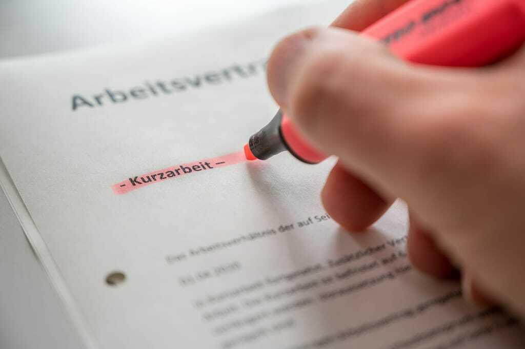 Hand markiert mit Stift Wort Kurzarbeit im Arbeitsvertrag.