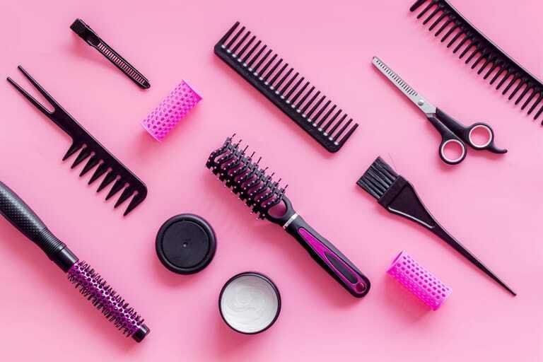 Friseurutensilien wie Schere oder Bürste auf pinkem Hintergrund.