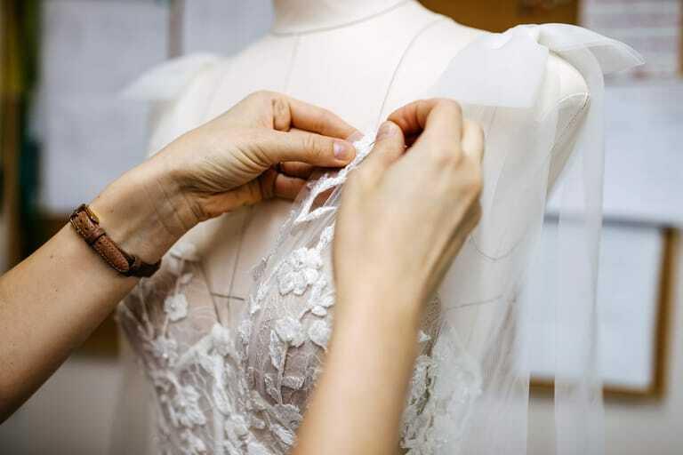 Maßschneiderin steckt Brautkleid an Puppe