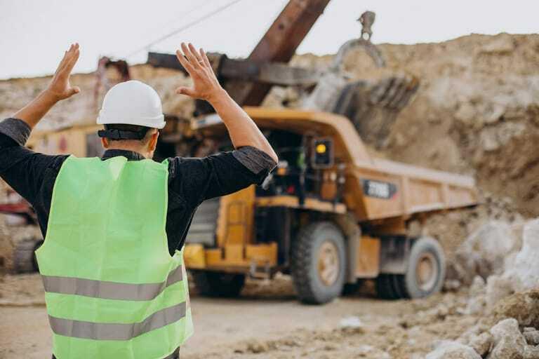Bauarbeiter mit Planierraupe in Steinbruch.