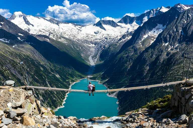 Wanderer und Hund genießen Aussicht auf Hängebrücke an der Olpererhütte.