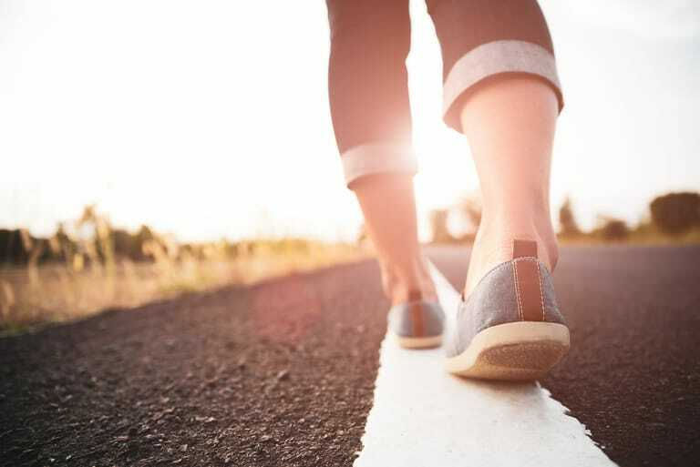 Frau geht Straße entlang, Nahansicht der Beine.