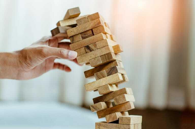 Hand hält stürzenden Turm aus Bauklötzen.