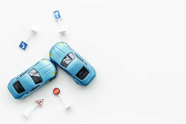 Zwei Spielzeugautos und -schilder auf weißem Hintergrund.