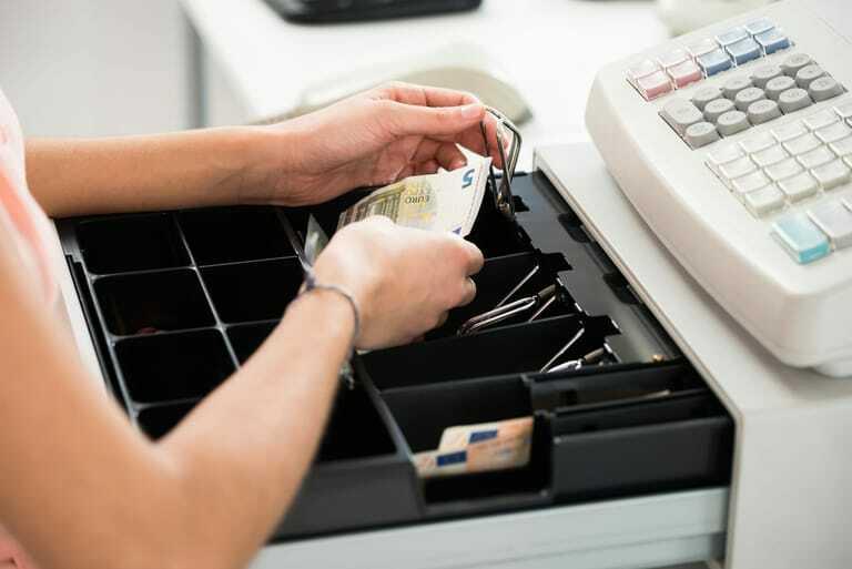 Weibliche Hand legt Geldschein in Kasse.