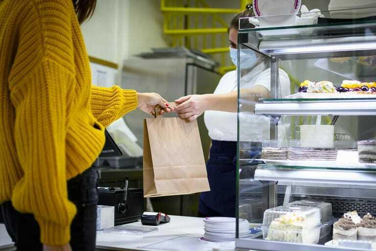 Verkäuferin in Bäckerei händigt Kundin Tüte aus.